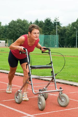 disabled sports: Disabled athlete at the starting line with her walker. Caricature picture to illustrate disability, ability, getting older, not wanna quit.