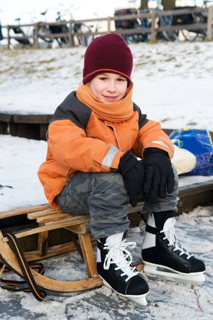sledging people: Little boy resting on a sled after skating Stock Photo