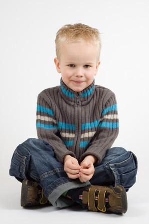 Cute little boy sitting crosslegged
