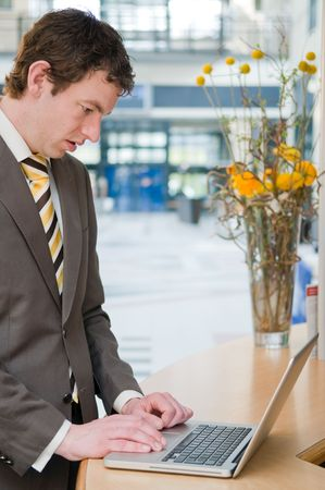 Young businessman working on a laptop standing at the front desk Stock Photo - 4718420