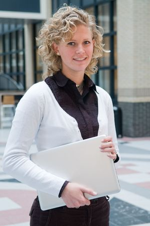 Young attractive businesswoman holding her laptop at the office Stock Photo - 4718461