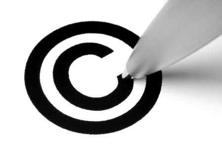 Copyright sign with tip of pen, on white.