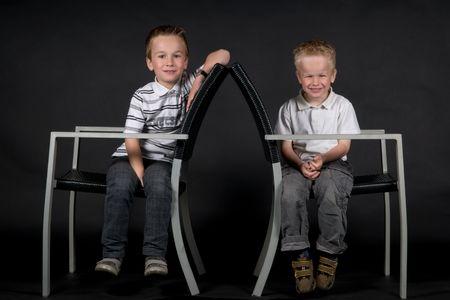 Dos hermanos sentados en una silla contra un fondo negro. Foto de archivo - 5473963