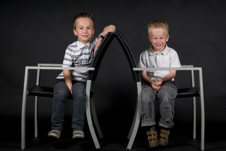 Two brothers sitting on a chair against a black background. photo