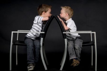Two brothers sitting on a chair looking at each other, against a black background. photo