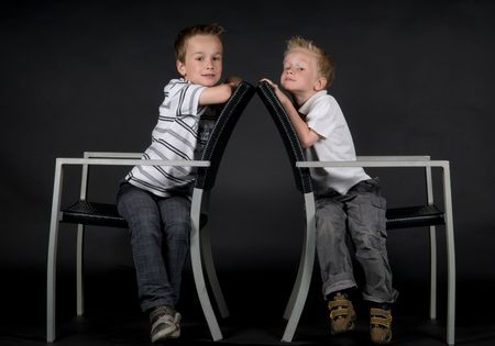Two brothers sitting on a chair, against a black background. photo