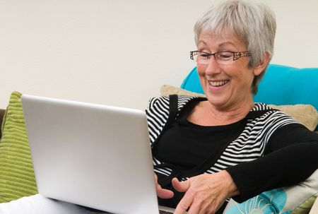 Senior woman working on a laptop, sitting relaxed on the couch. Stock Photo