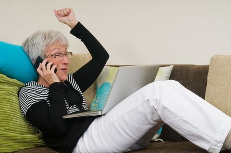 Senior woman working on a laptop, lying relaxed on the couch. Stock Photo