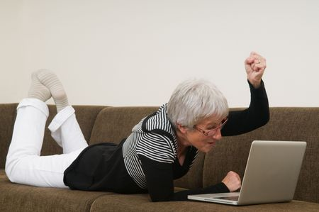 Senior woman working on a laptop, lying relaxed on the couch. photo
