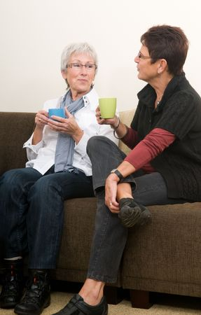 Two senior women drinking coffee, chatting and having a good time together as girl-friends. photo