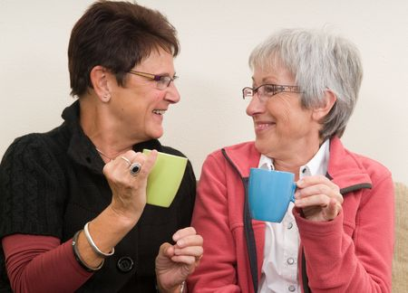 Two senior ladys drinking coffee together and having a good time. Фото со стока