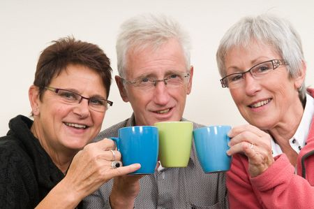 Three seniors holding a cup of coffee. Фото со стока