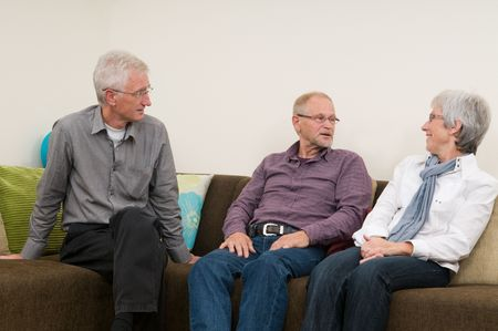 discussion group: Group of three seniors talking and laughing on a couch at home.