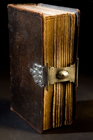 Nice old bible with an old lock on a black background. Stock Photo