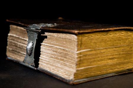historias biblicas: Biblia viejo agradable con un antiguo bloqueo sobre un fondo negro.