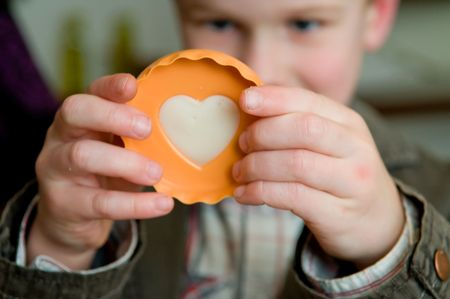 Little boy going to bake a cookie in the shape of a heart.