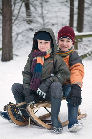 Two young boys sitting on a sled in the snow. photo