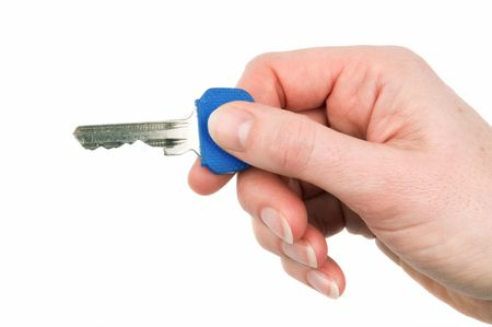 doorkey: Womans hand holding a key, against white background. Stock Photo