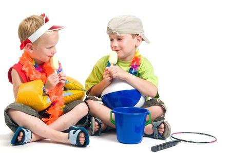 Two boys ready to go on vacation, enjoying their first icecream. photo