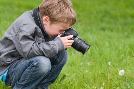 slr camera: Young boy, nine years old, already practicing with an SLR shooting pictures of nature.