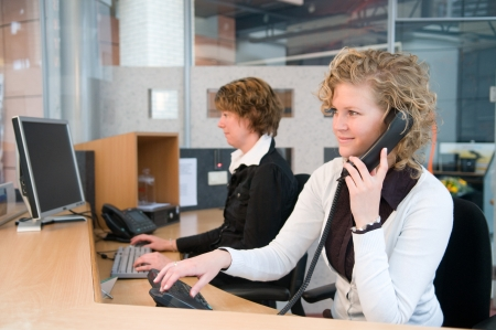 Two professional women working at a front desk. Stock Photo