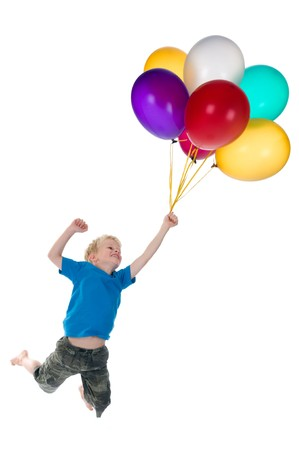 Little boy flying behind a bunch of balloons, isolated on a white background. Stockfoto