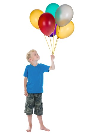 studioshoot: Happy boy holding a bunch of balloons, against a white background.