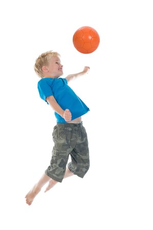 Young boy going to make a header. Will he score? Isolated on a white background. Little movement in arms and legs. photo