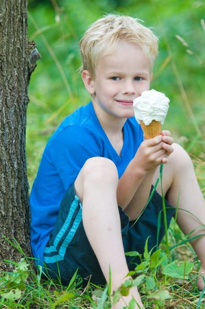 Seven year old boy enjoys eating a big icecream on a hot summerday, while sitting against a tree. photo
