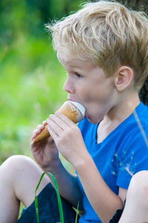 seven year old: Seven year old boy enjoys eating a big icecream on a hot summerday, while sitting against a tree. Stock Photo