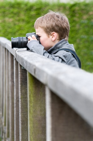 9 year old: A 9 year old boy is practising with his fathers camera.