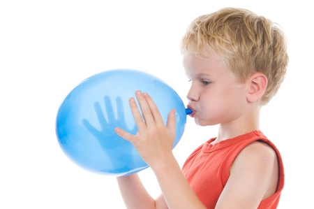 Little boy is blowing up a balloon, against a white background.