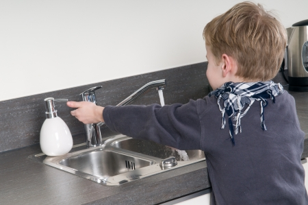 Child washing his hands before he is going cooking. photo