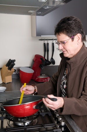 Senior woman in a modern kitchen cooking a meal. photo