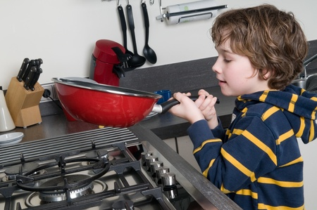 Young boy learning to cook in a modern kitchen photo