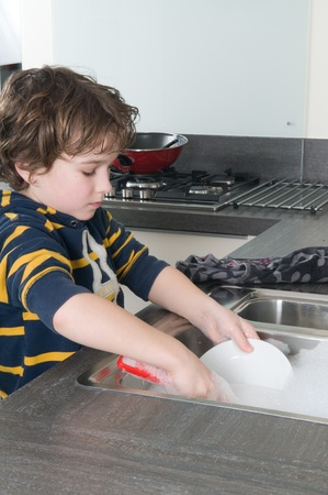 Boy doing the dishes in a modern kitchen photo