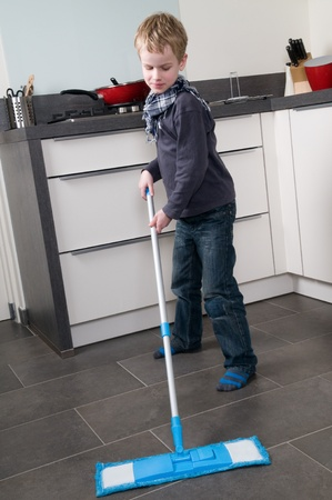 Young boy is learning how to clean a floor photo