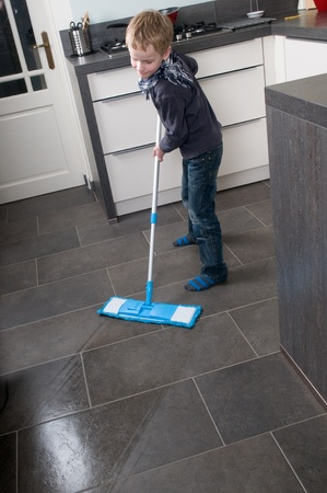 Young boy is learning how to clean a floor Stock Photo - 8789318