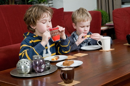 Two brothers drinking and eating something in a livingroom