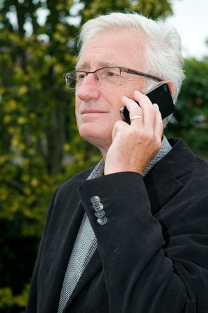 Businessman using a smartphone while being outside photo