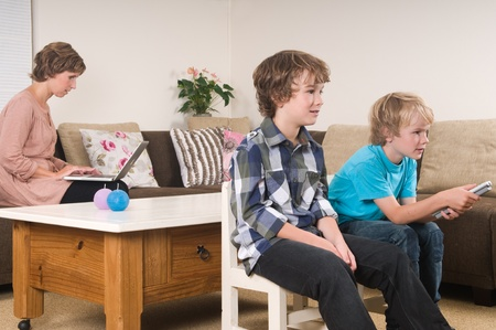 kids laptop: Children are watching tv while mother is working in the background Stock Photo