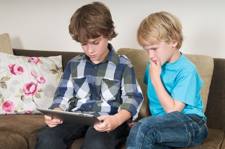 Kid is working on a tablet computer while his brother is watching Stock Photo - 10483478