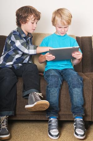 Малыш работает на планшетном компьютере в то время как его брат наблюдает Фото со стока