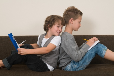 Two friends doing their homework in the livingroom on the couch photo