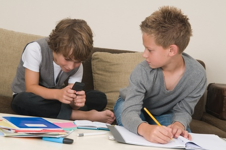 not ready: Two friends doing their homework in the livingroom. One of them is gaming, the other one is not ready and is jealous.