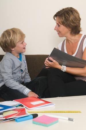 Мальчик делает свою домашнюю работу в гостиной, а мать помогает ему