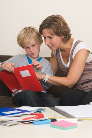 Boy is doing his homework in the livingroom while mother is helping him Stock Photo - 10641274