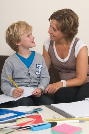 Boy is doing his homework in the livingroom while mother is helping him photo