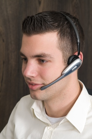 contact center: Male receptionist working at a helpdesk in an office