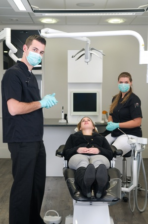 male dentist: Dentist in the front, nurse and patient in the background Stock Photo